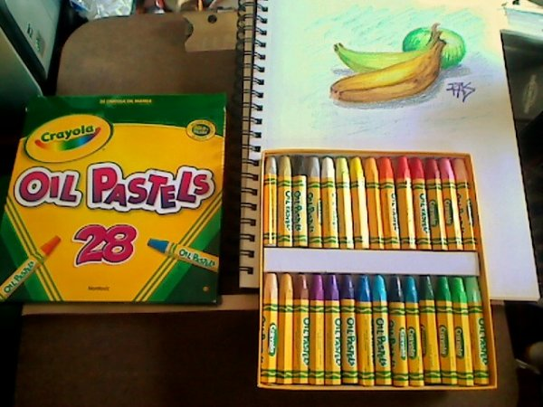 Photo of Crayola oil pastels with box lid and sketchbook with drawing of bananas and green apple.